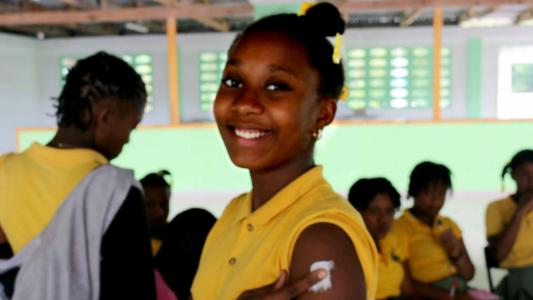 Girl in yellow shirt smiles after HPV vaccine shot