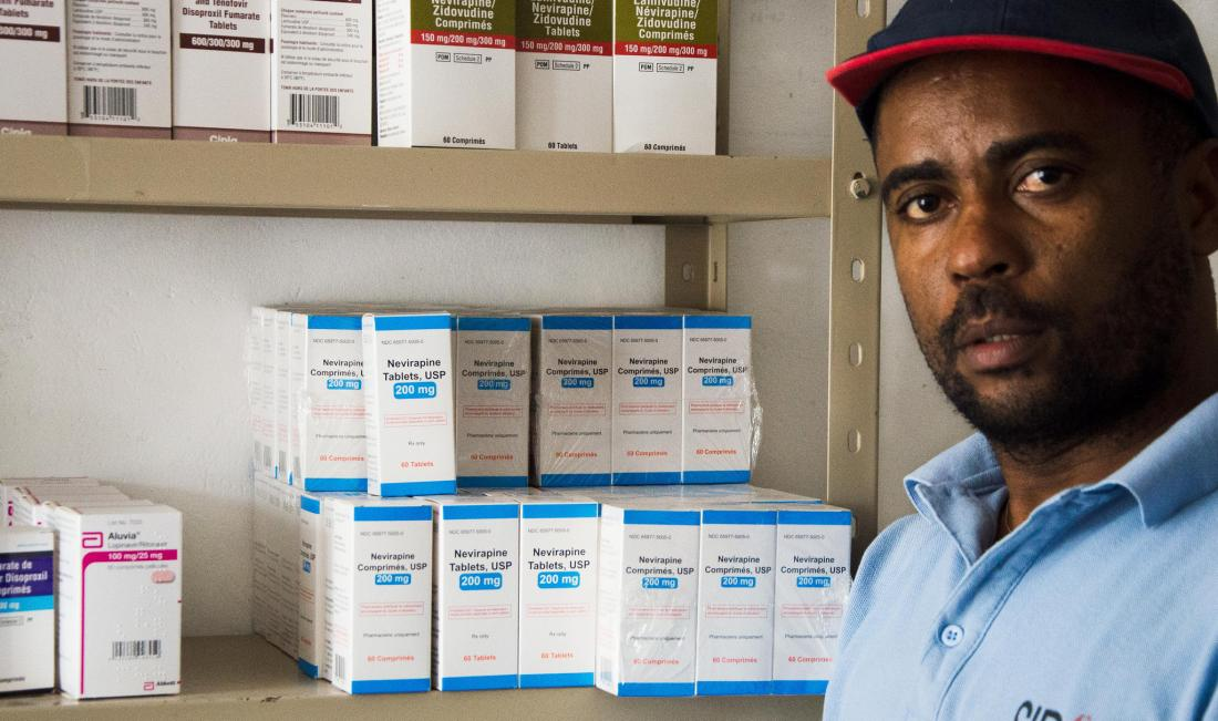 Rene standing in front of a shelf of hiv medications