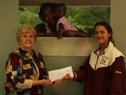 Camille give Nanette, the St. Boniface co founder, a check