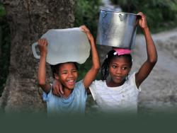 two young girls carrying bucks of water on their heads and smiling
