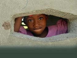 Young girl looking through a hole in the wall