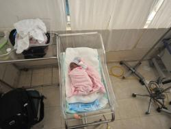 Infant with pink blanket laying in the NICU