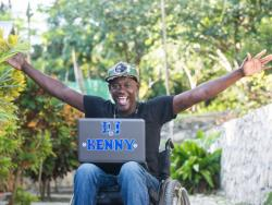 "Kenny smiling with computer labelled ""DJ Kenny"""