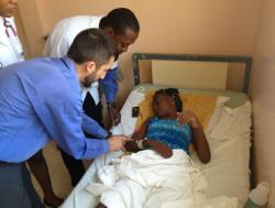 Two doctors checking on a patient laying in bed