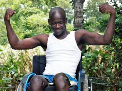 Man in wheelchair flexing his muscles