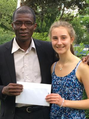 Daisy handing check to dr. pierre