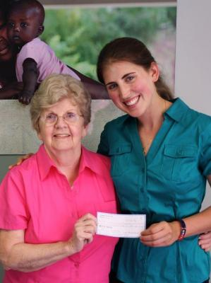 Leader of students for Haiti handing Nanette, the St. Boniface co-founder, a check